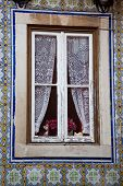 picture of lace-curtain  - Window with lace curtains and a surround of ornate patterned tiles - JPG