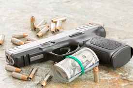 stock photo of handgun  - Conceptual image of a handgun with a roll of money surrounded by scattered bullets and cartridges on an old weathered wooden surface with copyspace depicting crime a payoff robbery or bribe - JPG