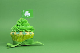 stock photo of shamrocks  - Happy St Patricks Day green cupcake with shamrock flag on green background with copy space for your text here - JPG