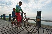 MANDALAY, MYANMAR - JAN 19, 2014: Unidentified Burmese woman and her child crossing U Bein bridge by