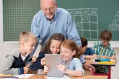 picture of classmates  - Cute happy young children in class at school smiling happily as they read something on a tablet computer under the watchful eye of a male teacher - JPG