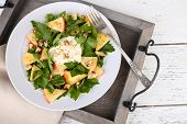 Green salad with apples, walnuts and cheese on plate, on tray, on wooden background