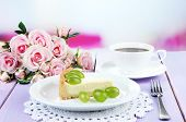 Slice of cheesecake with grape berries on plate, on wooden table, on bright background
