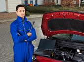 Mechanic With Arms Crossed Holding Wrench By Car