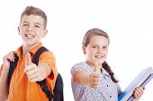 Happy school kids with thumbs up, isolated on white background