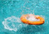Orange Life Buoy Is Thrown To Clear Water Swimming Pool