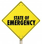 State of Emergency words on yellow road sign to warn of an impending crisis or disaster ahead