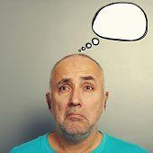 portrait of sorrowful senior man with white speech balloon over grey background