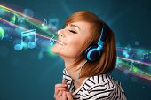 Pretty young woman with headphones listening to music, glowing notes and lines concept