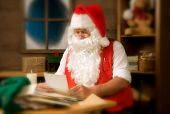 Santa Claus in his workshop reading letters and surrounded by toys and presents. Instagram feel with