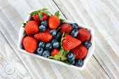 A rectangular bowl full of berries. Blueberries and strawberries on a rustic wooden kitchen table.