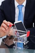 Businessman Pushing Smartphone In Shopping Cart