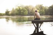 picture of dock a lake  - Boy with no friends sitting at the lake on a dock looking at the water in summer - JPG