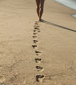 stock photo of footprint  - Young woman walking alone on the sand beach in the sunset and leave footprints behind - JPG