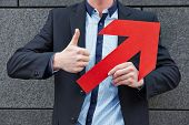 Man with red arrow leaning on wall and holding thumbs up