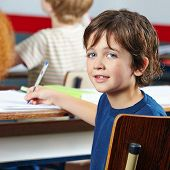 Smiling child sitting at table in elementary school class