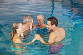Family with senior couple creating circle in water of swimming pool