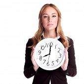 Portrait of beautiful blond woman wearing suit holding in hands clock, isolated on white background,