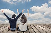 Asian couple sit on wooden ground and feel exciting against the dramatic sky with copyspace.