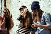 Girls having fun together outdoors using smart phone, lifestyle. Instagram effect.
