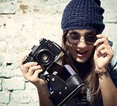 Retro photographer. Modern urban girl has fun with vintage photo camera outdoor near grunge wall, im