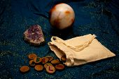 picture of rune  - A plain muslin bag with wooden runes spilling out over a sparkling blue cloth with amethyst and crystal ball in the background - JPG