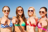 summer vacation, holidays, travel, gesture and people concept - group of smiling young women pointin