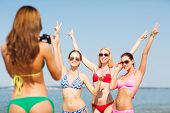 summer vacation, holidays, gesture and people concept - group of smiling women photographing by came