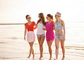 summer vacation, holidays, travel and people concept - group of smiling young women in sunglasses an