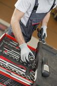 High angle view of male mechanic arranging tools in drawer at car repair shop
