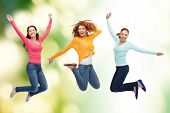 happiness, freedom, ecology, friendship and people concept - group of smiling young women jumping in