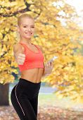 sport, fitness, technology, internet and healthcare concept - smiling sporty woman with smartphone s