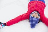 Portrait of smiling young woman lying on snow