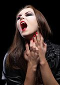 Young beautiful vampire woman on black
