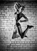 Muscular woman on grey brick wall (monochrome version)