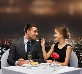 restaurant, couple and holiday concept - smiling couple eating dessert at restaurant