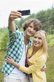 pic of two women taking cell phone  - Happy young couple taking self portrait through cell phone in field - JPG