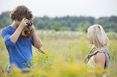 Young man photographing woman in field