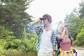Young couple using binoculars while hiking in forest