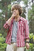 Young man smoking in forest