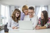 Family of four using laptop together at table in home