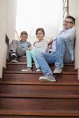 Full length portrait of father and children sitting on steps at home