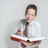 Smiling schoolboy reads a big red book
