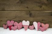 Handmade Red White Checked Hearts On A Wooden Christmas Background.