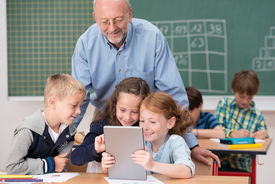 image of senior class  - Cute happy young children in class at school smiling happily as they read something on a tablet computer under the watchful eye of a male teacher - JPG