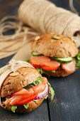 Sandwiches with salmon and vegetables on wooden background