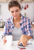 Young woman reading mgazine In kitchen at home