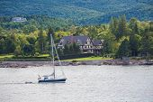 Постер, плакат: Blue Sailboat Past Tudor Mansion