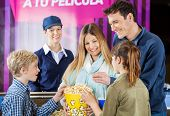 Happy family of four enjoying popcorn while female worker standing at cinema concession counter