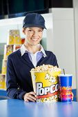 Portrait of happy female worker with popcorn and drink at concession counter in cinema